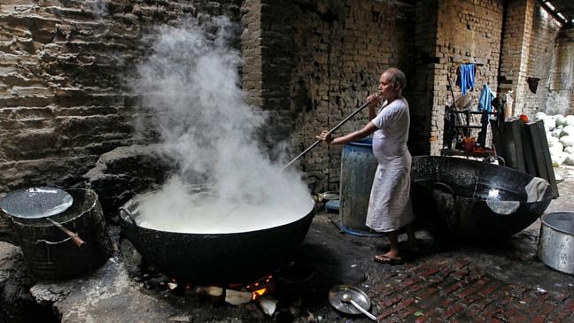 Un operaio prepara caramelle di zucca dolce conosciute con il nome di Petha in una fabbrica in Allahabad